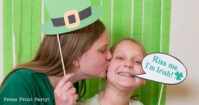 St. Patrick's day free photo booth props printables. girl with Leprechaun hat kissing girl with kiss me I'm Irish sign by Press Print Party!