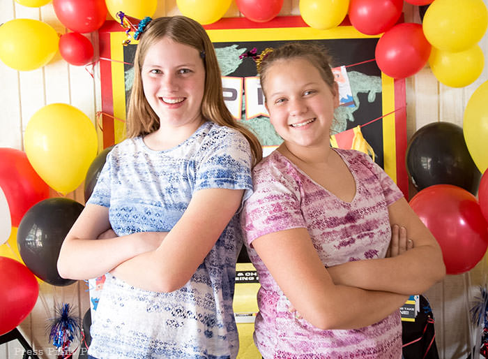 2 birthday girls in front of backdrop - The amazing race party ideas - Press Print Party!