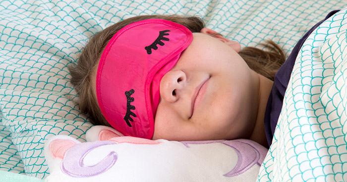 sleeping girl with eye mask with eyelashes and unicorn pillow