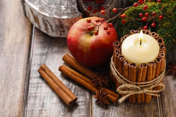 Candle stick with cinnamon sticks around to make a diy gift for mom for christmas