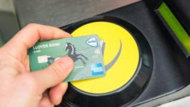 A Lloyds credit card tapped on an Oyster Card reader