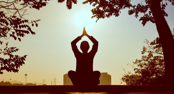 person doing yoga with hands overhead