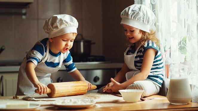 kids sitting on the kitchen counter wearing chef hats rolling out pizza dough