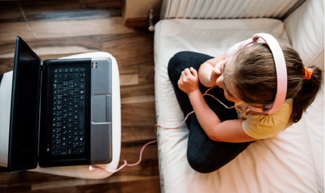 child wearing headphones streaming from laptop