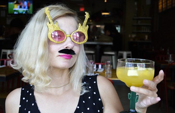 woman in Elton John glasses and moustache