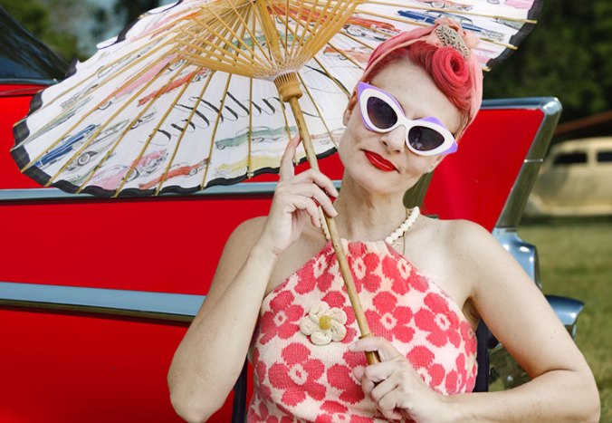 Retro red haired woman wheelchair street style with hair crayon and Prabal sunglasses