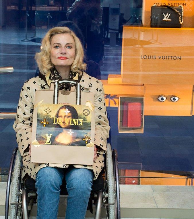Pretty Cripple holding DIY Mona Lisa Vuitton Koons shopping bag