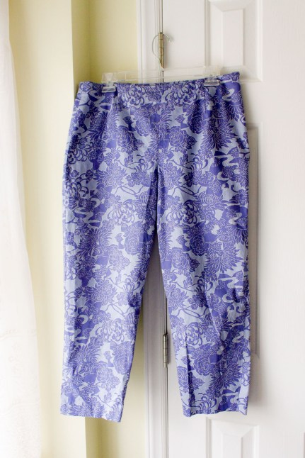 Purple print pants hanging on a hanger.