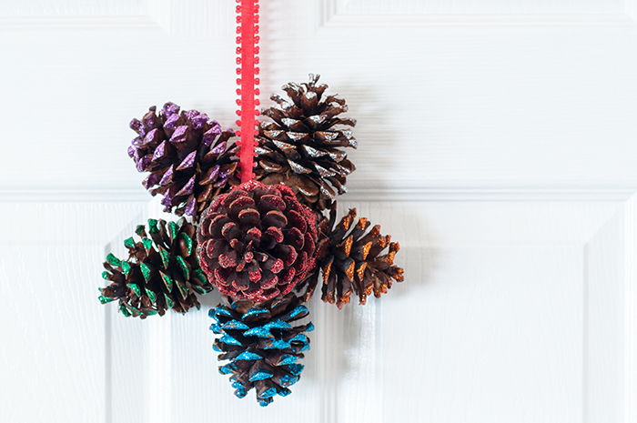 how to make a glittered pine cone door hanger