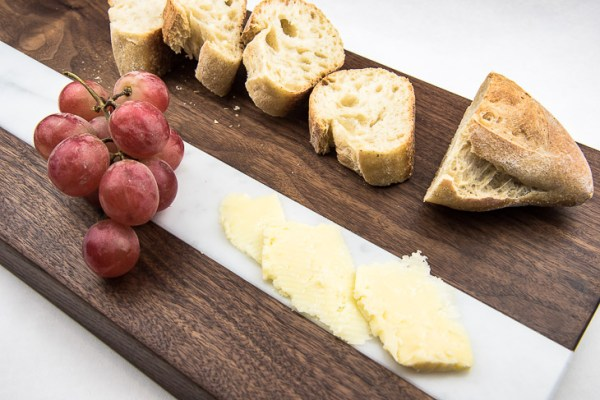 This bread and cheese board is multi-functional! Cut bread on the wood section, and cheese on the marble! Pair with grapes for the perfect appetizer display!