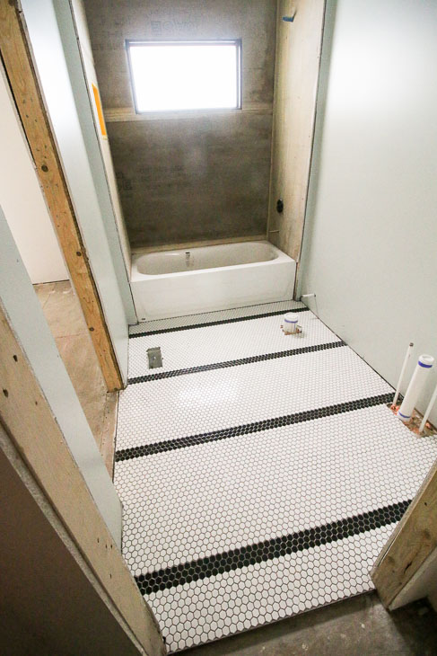 black stripes in small white hex tile field on bathroom floor