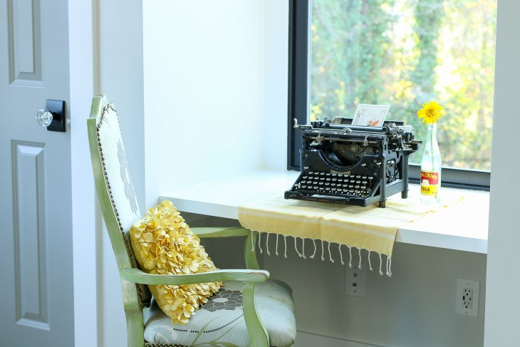vintage typewriter on desk by window between closets