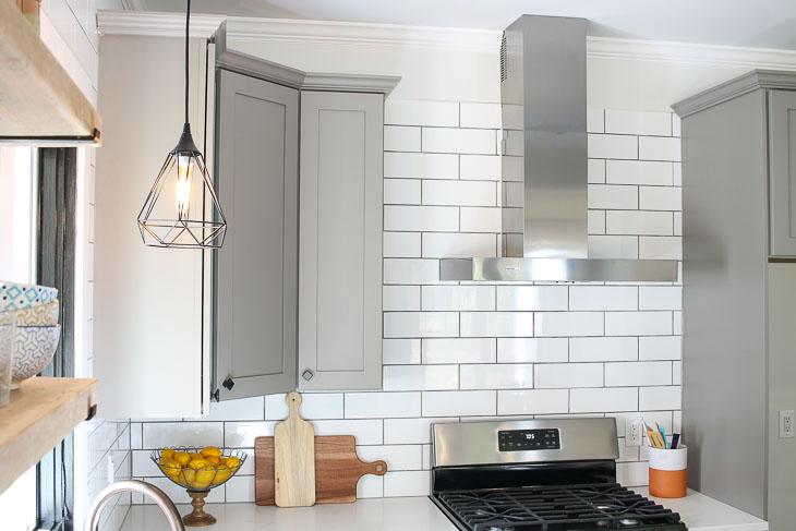 Subway tile backsplash, gray shaker cabinets, stainless steel range hood from Broan