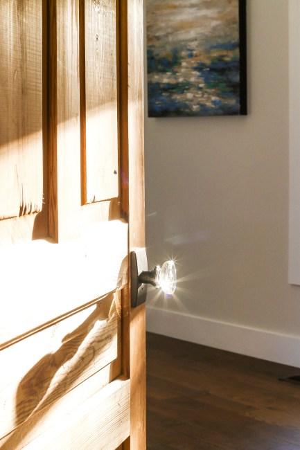 Sun glinting off glass door knob on raw wood door