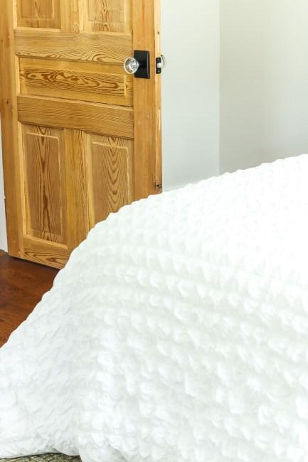 bedroom with 1900 wood door and glass door knob in the background