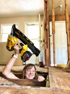 pretty handy girl in crawlspace with framing nailer extended over head