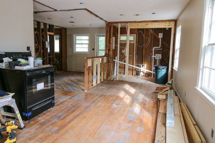 view into living room and kitchen walls down to studs and framing