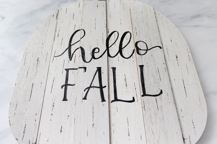 white wooden pumpkin with hello fall written on it