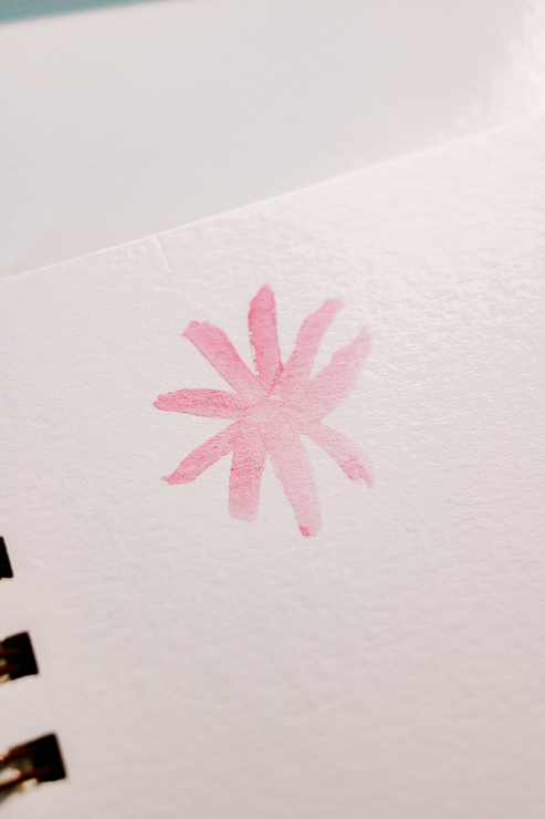 a pink watercolor flower being painted
