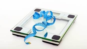 Skleněná váha a modrý krejčovský metr
