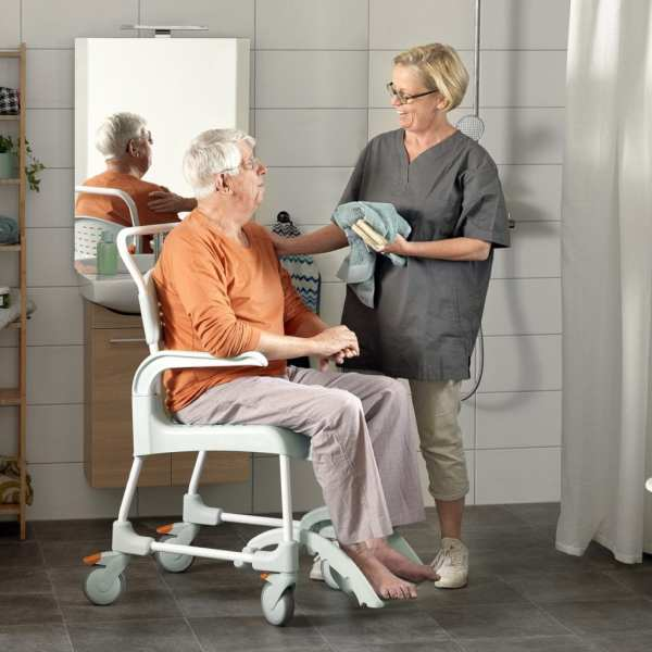 Etac-clean-mobile-shower-commode- carer with user