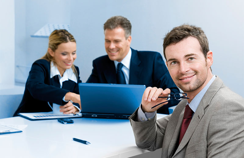 Smiling satisfied businessman looking at camera with his colleagues in the background during a meeting in the office