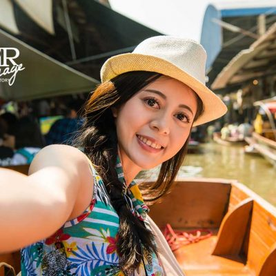 attractive beautiful asian women having fun taking selfie self-portrait photo on the boat of floating market journey in Thailand, holiday and travel vacation concept