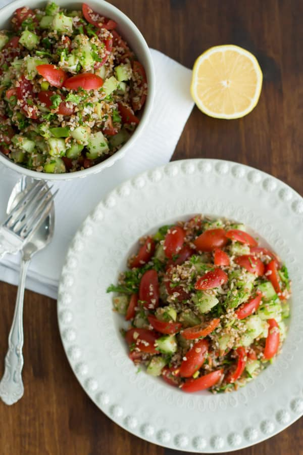 Plate and bowl of Tabbouleh made with bulgur, cherry tomatoes, cucumbers, parsley, mint, and scallions