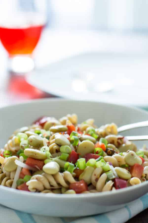 close up of pasta salad with lima beans and anchovies topped with sliced scallions