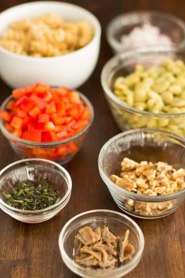 cut pasta salad ingredients in prep bowls: whole feel fusilli, baby lima beans, bean sprouts, red onion, red peppers, fillets of anchovies, chopped fresh thyme