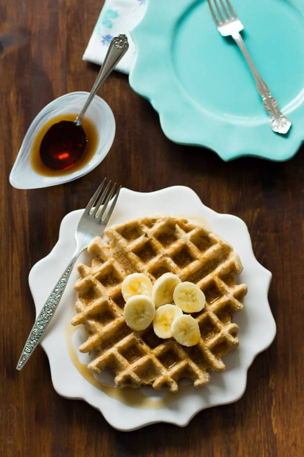 peanut butter waffles topped with sliced bananas with maple syrup drizzled on top.