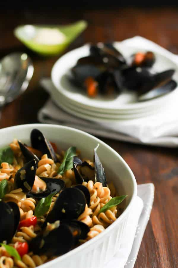 Close up of Whole Wheat Fusilli with Mussels with a plate of mussels in the background