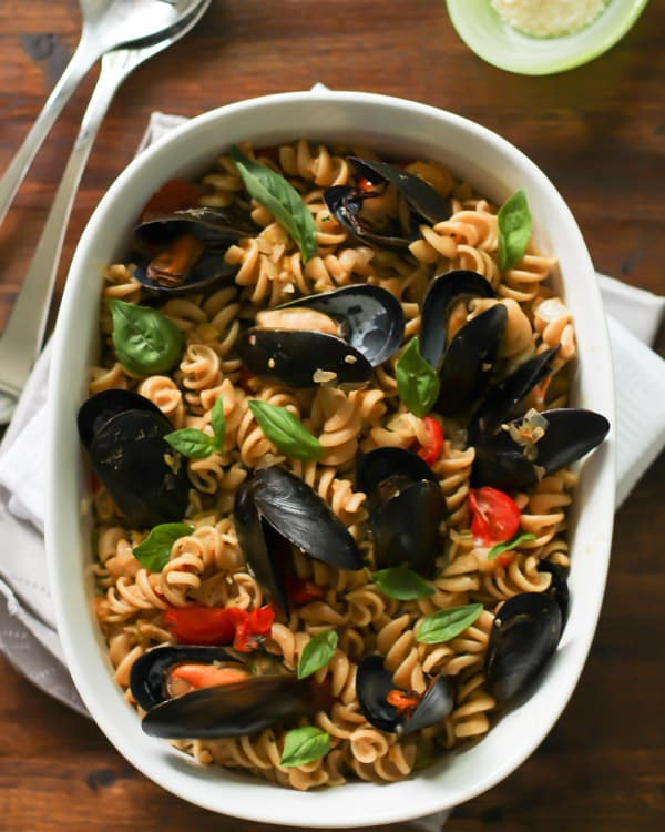 White baking dish with Whole Wheat Fusilli with Mussels and cherry tomatoes inside with basil on top