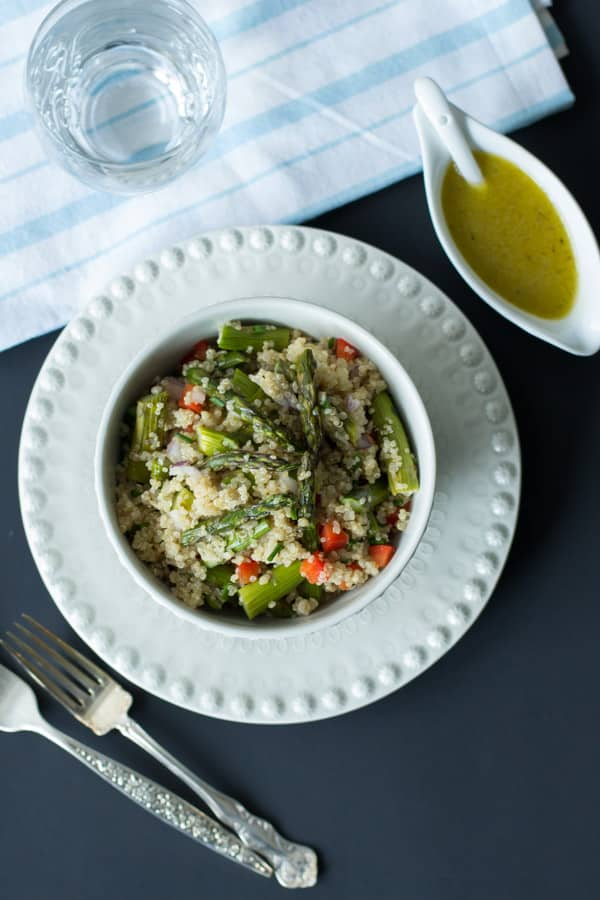 quinoa salad with roasted asparagus in with bowl with dressing on the side