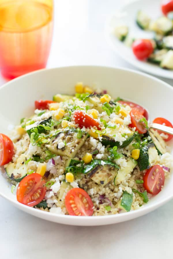 A white bowl of couscous salad with zucchini.