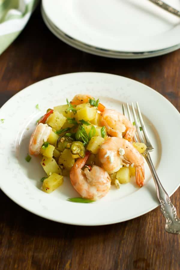 baked potato with lemon shrimp on a plate