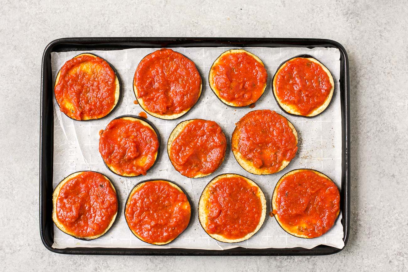 raw slices of eggplant with tomato sauce on the top on a baking sheet