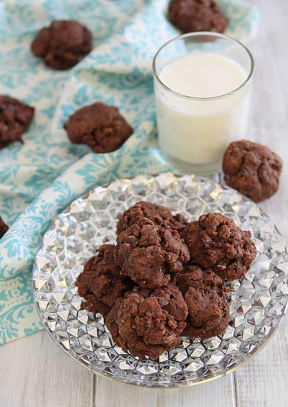 A plate of amaretto fudge cookies with a glass of milk.