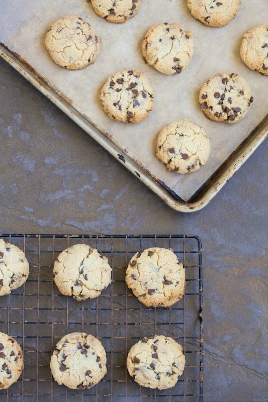 Chocolate chip cookies in a sheet pan and on a cooling rack.