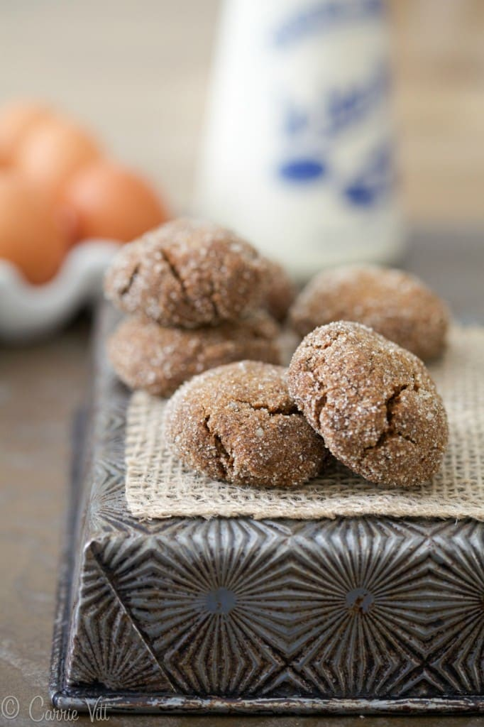 Molasses cookies on top of a baking pan.