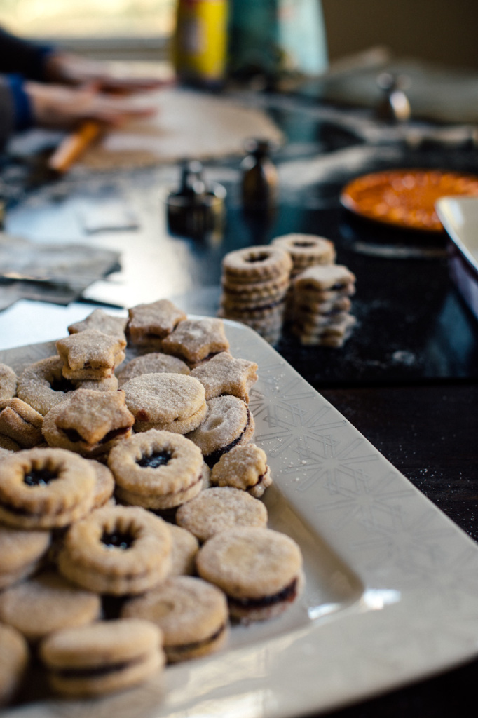 Multiple spitzbuben cookies in a platter while in the background, dough is being rolled out.