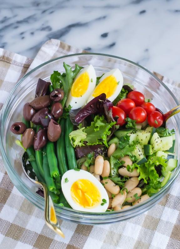 A glass bowl of vegetarian salad nicoise.
