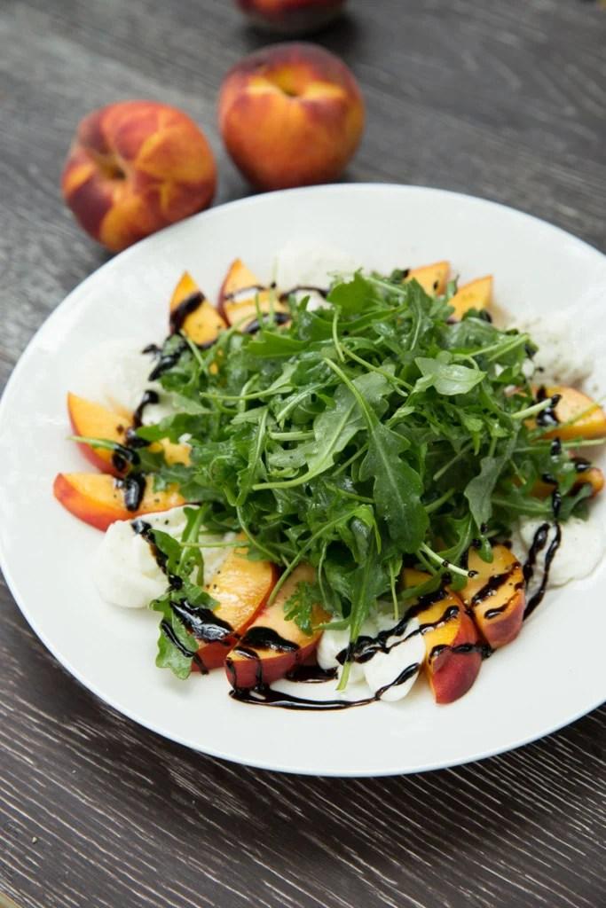 A white plate of peach and burrata arugula salad.