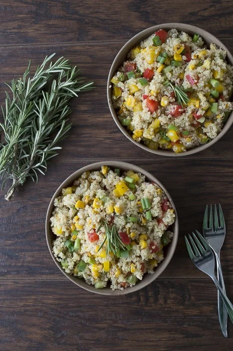 Overhead photo of two bowls of quinoa bell pepper salad with rosemary.