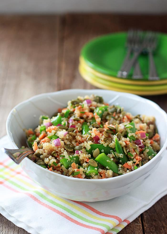 A white bowl with quinoa confetti salad with sugar snap peas with toasted pepitas.