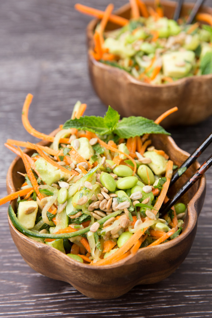 Two wooden bowls of cucumber carrot noodle thai salad.