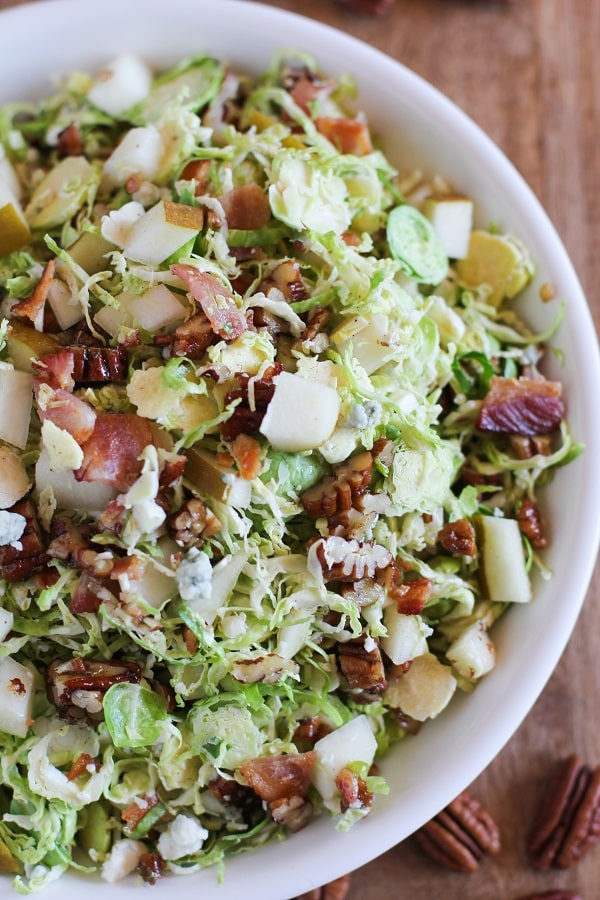 A close up of a bowl of brussels sprout chopped salad with warm bacon dressing.