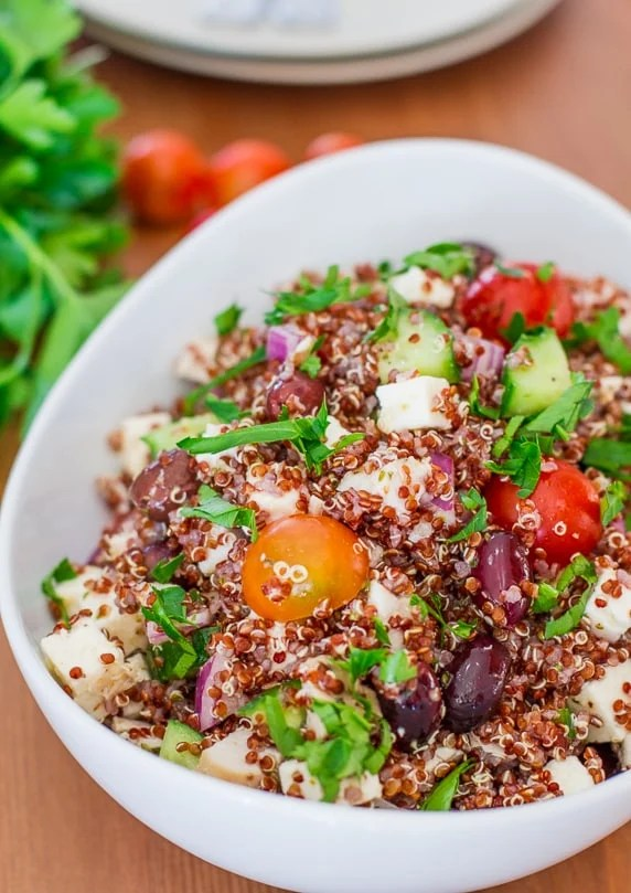 A large white bowl of greek chicken red quinoa salad.