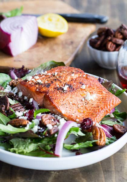 Seared salmon on top of a plate of salad.