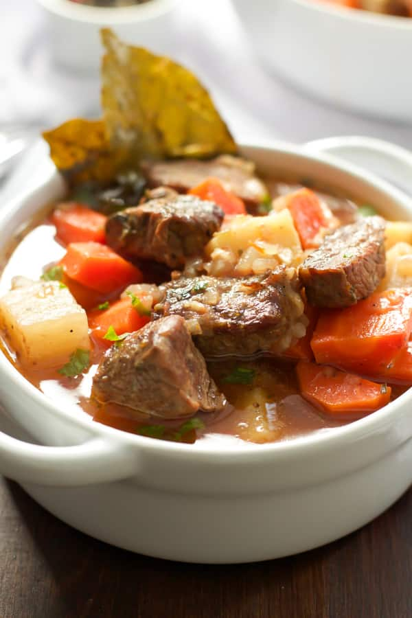 Close up of a bowl of stew with beef and vegetables.